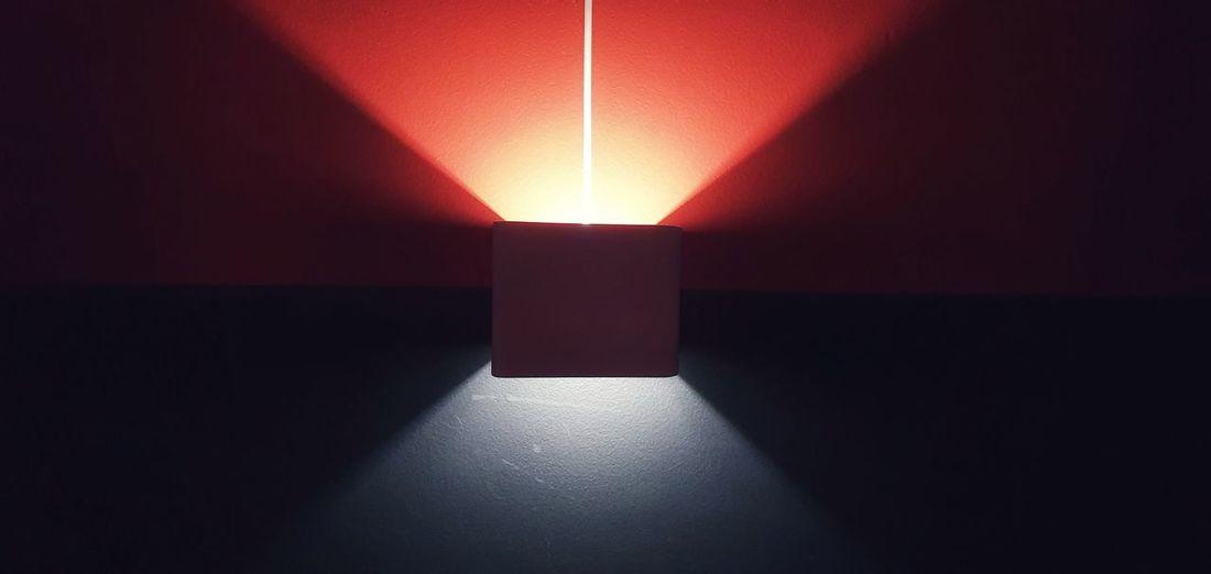 Sunlight falling on illuminated wall in darkroom