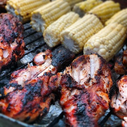 Chicken and corn being barbecued on grill