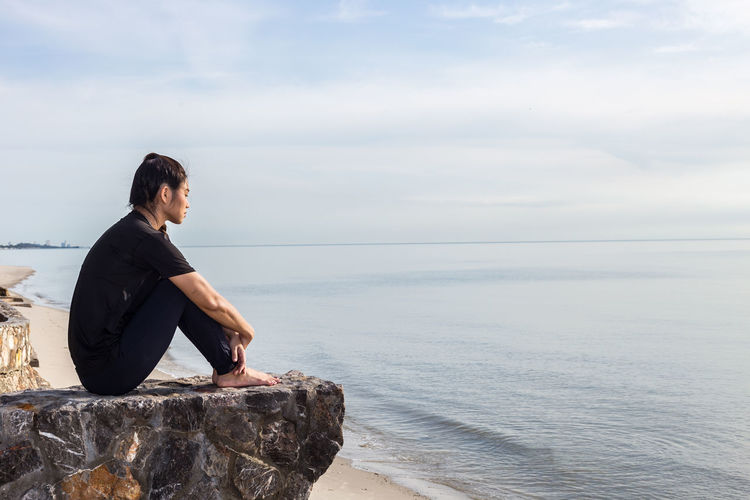 Side view of woman sitting on rock over sea against sky