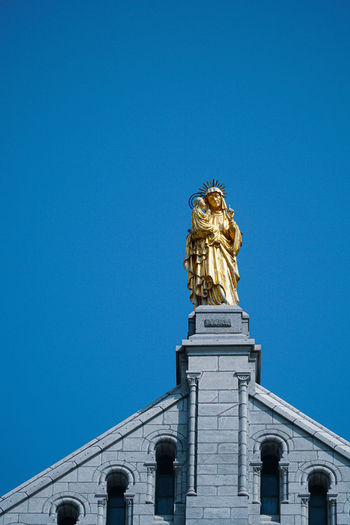 Low angle view of virgin mary statue on building against clear blue sky