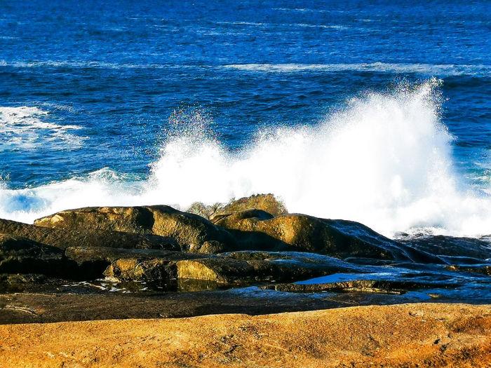 Water splashing on rocks by sea