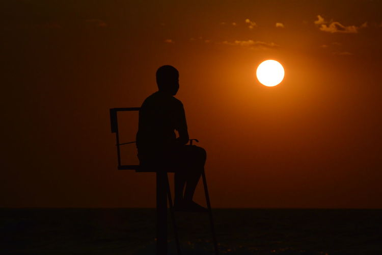 Silhouette man sitting on lifeguard chair at beach against sky during sunset