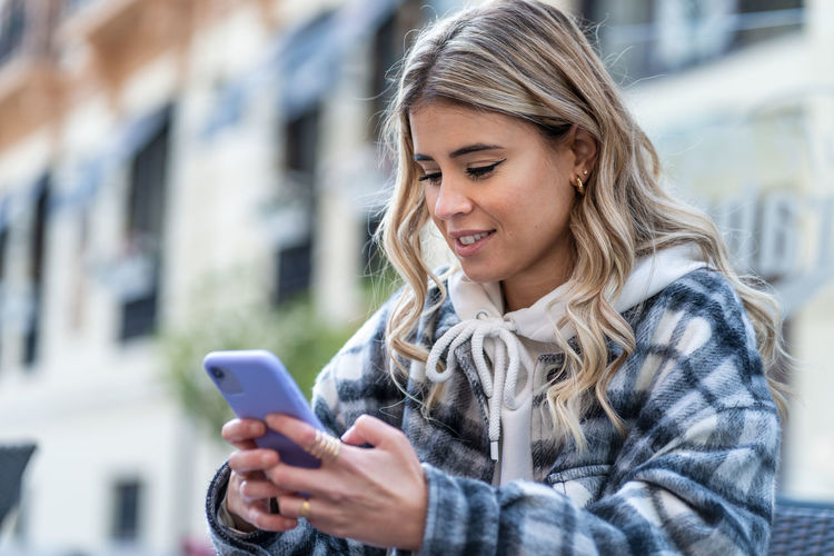 Young woman using smart phone outdoors