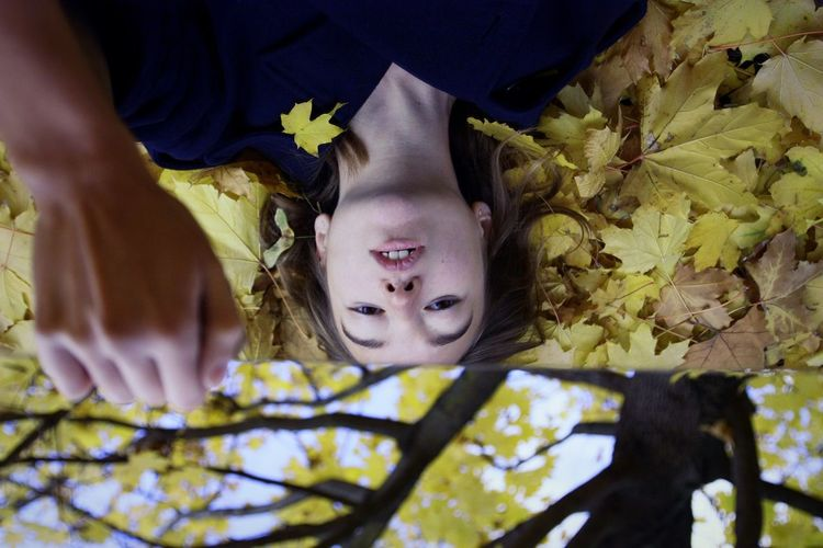 Portrait of cute girl lying on leaves during autumn