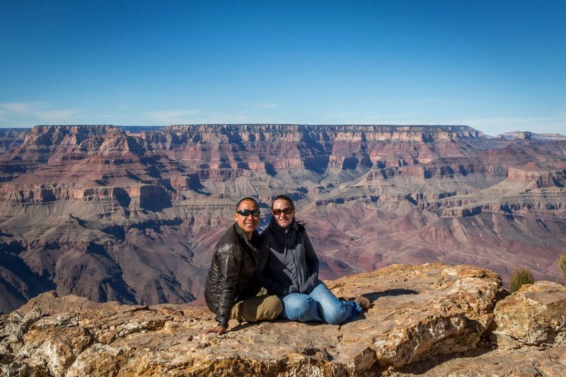 Portrait of couple sitting on rock formations against sky