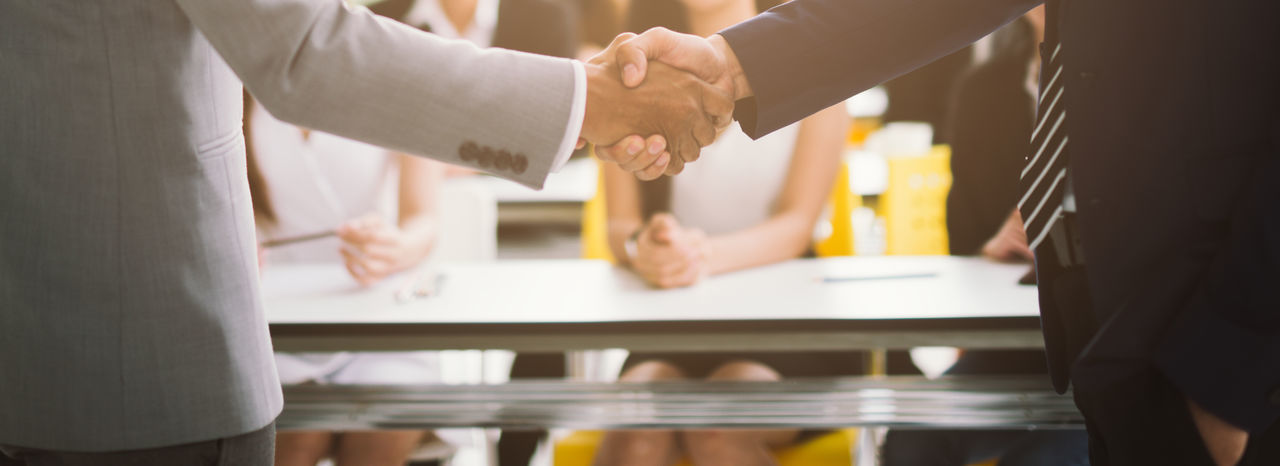 Midsection of businessman shaking hands
