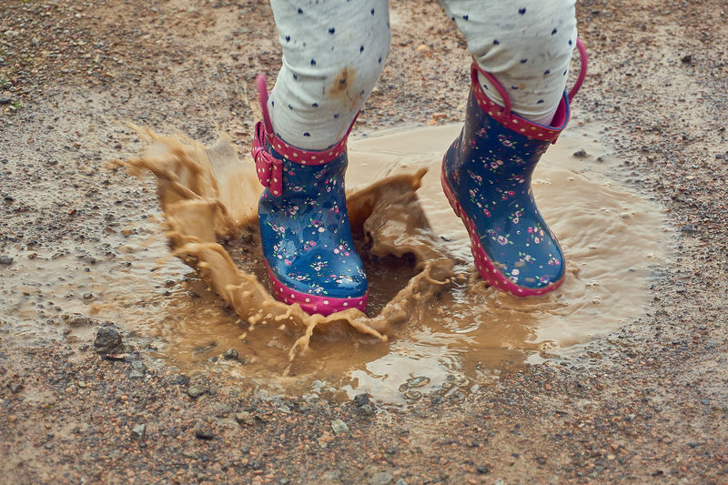 Child splashing in a puddle with wellington boots on Body Part Child Childhood Day Dirt Dirty Fun High Angle View Human Body Part Human Foot Human Leg Land Leisure Activity Lifestyles Low Section Messy Mud Nature One Person Outdoors Puddle Real People Rubber Boot Shoe Splashing