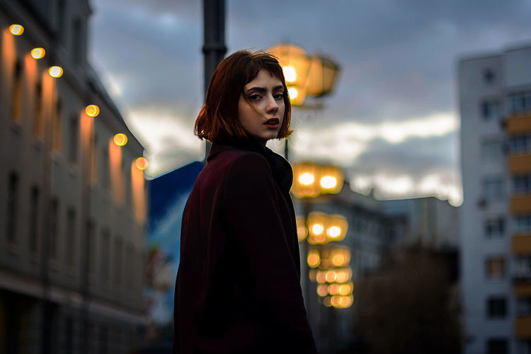 Portrait of young woman standing in illuminated city