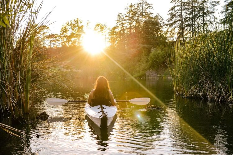 Rear view of woman kayaking on river