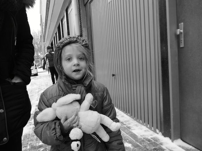 Portrait Of Girl Holding Stuffed Toy While Standing On Footpath