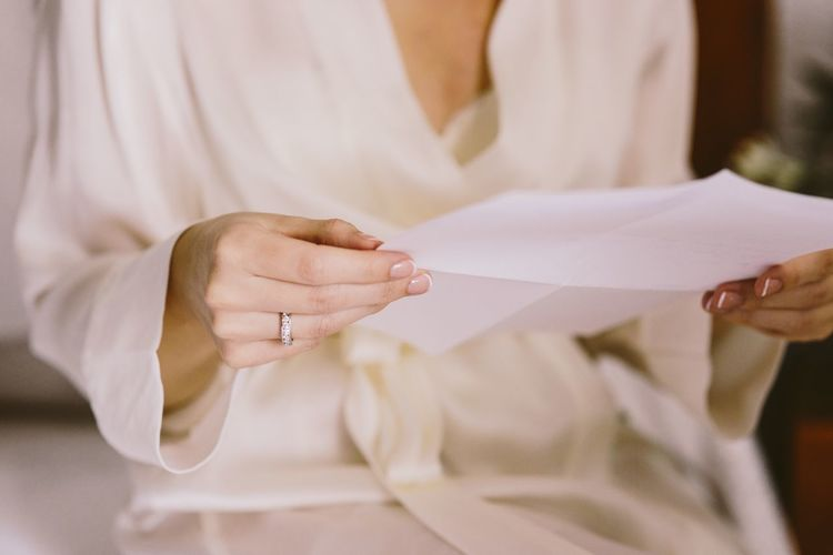 Midsection of woman holding paper