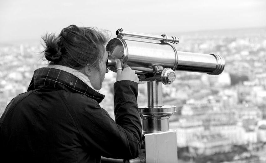 Woman looking through binoculars at city