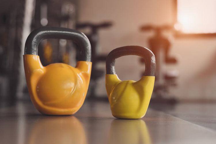 Two colorful kettlebells on fitness gym floor. Heavy weight sports equipment and accessories in workouts training club. Body building muscle and strength weightlifting. Lifestyle and indoors activity. Business Close-up Day Dumbbell Emotion Finance Fitness Focus On Foreground Food Food And Drink Group Of Objects Gym Indoors  Kettlebell  No People Selective Focus Simplicity Sport Sports Equipment Still Life Strength Strength Training Surface Level Two Objects Yellow