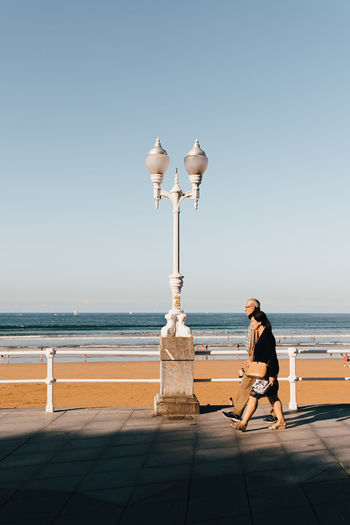 Man with umbrella against sea against clear sky
