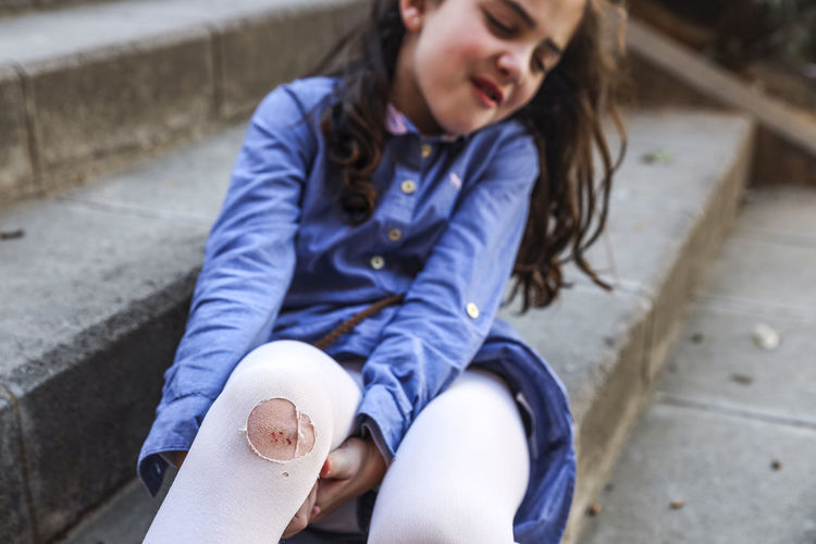 Girl with wounded leg sitting on steps