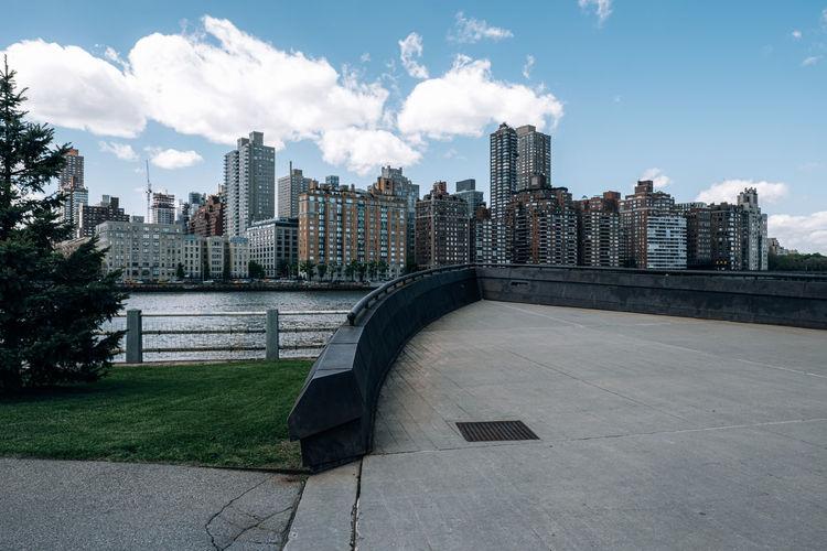 Modern buildings by river against sky in city