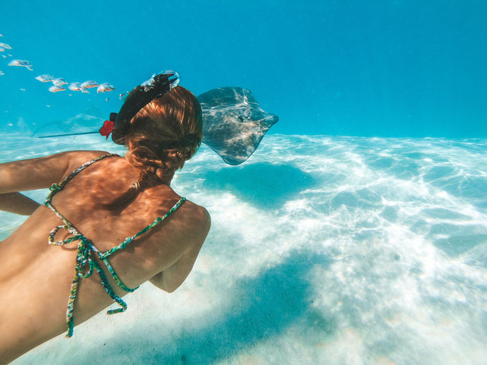 Rear view of woman swimming by stingray in sea