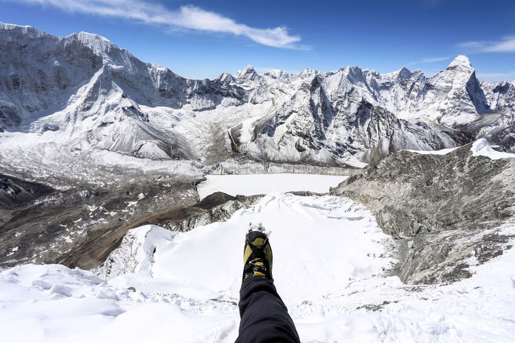 Low section of person on snowcapped mountains against sky