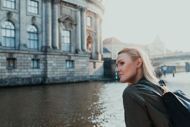 Portrait of young woman against building
