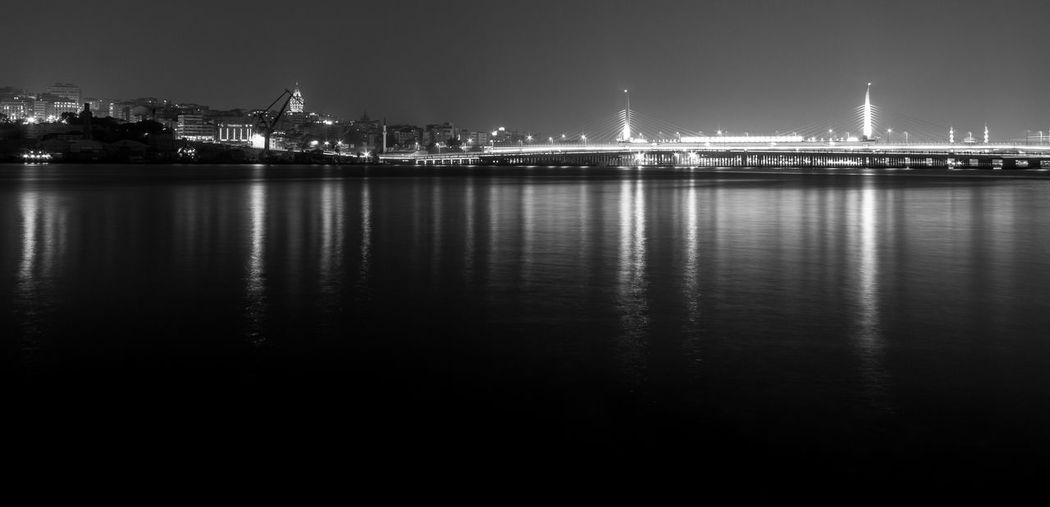 Panoramic view of illuminated bridge over river by city at night