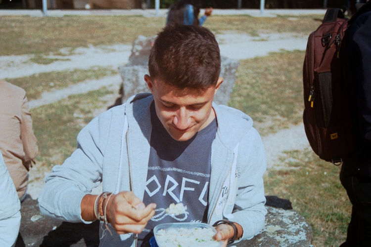Young man eating food on field