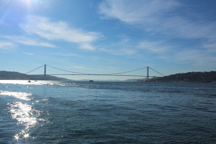 Bosphorus bridge in sea against cloudy sky