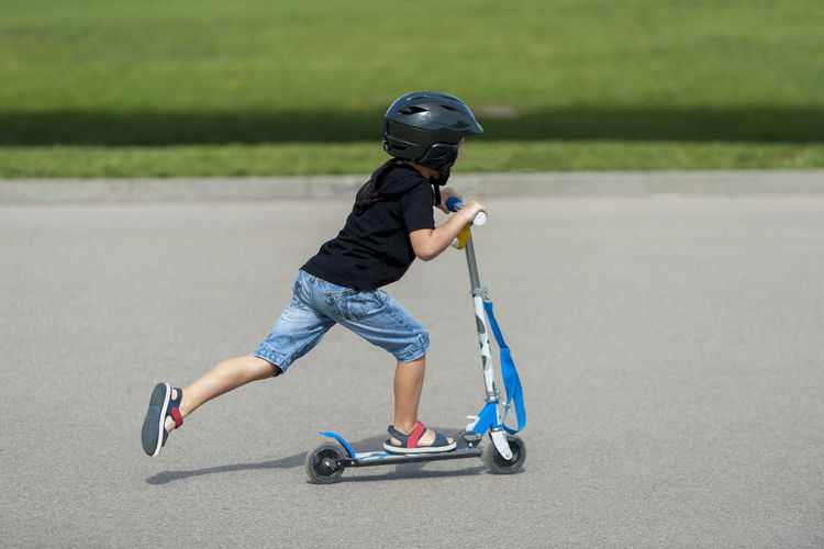 Side View Of Boy Riding Push Scooter On Road