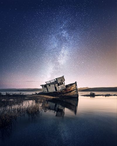 Shipwreck in lake against sky at night