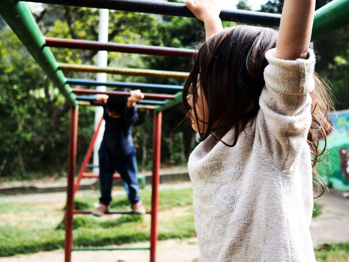 Low Angle View Of Girl And Boy Playing On Monkey Bars At Playground