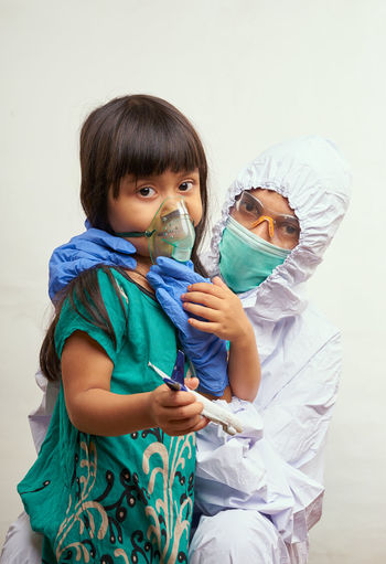 Portrait of doctor with girl wearing mask against white background