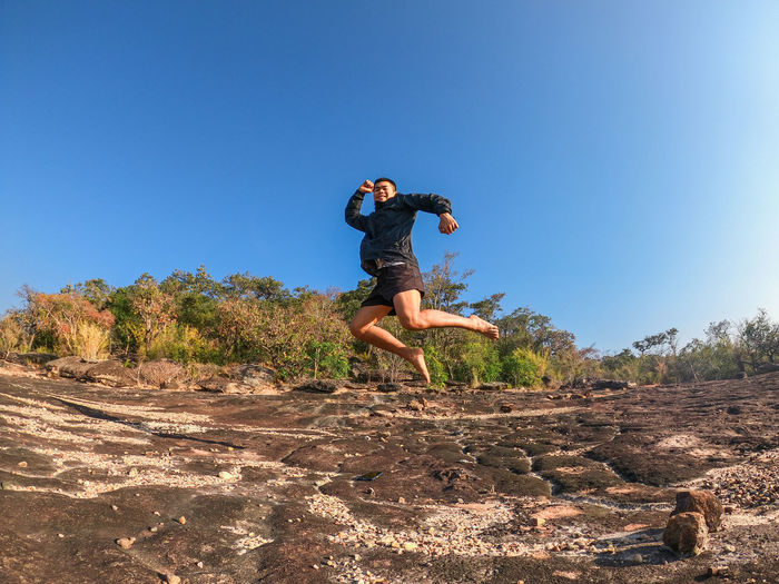 Full length of man jumping against clear sky