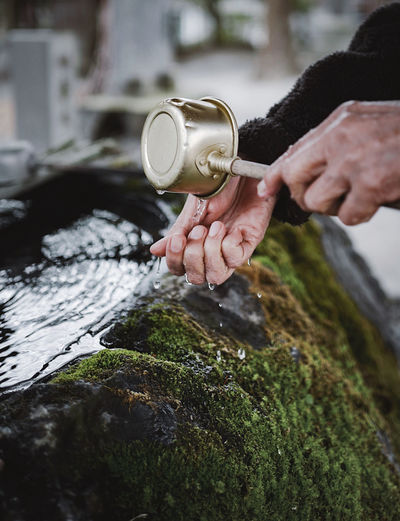 A hand shot of old lady washing her hands in japanese temple