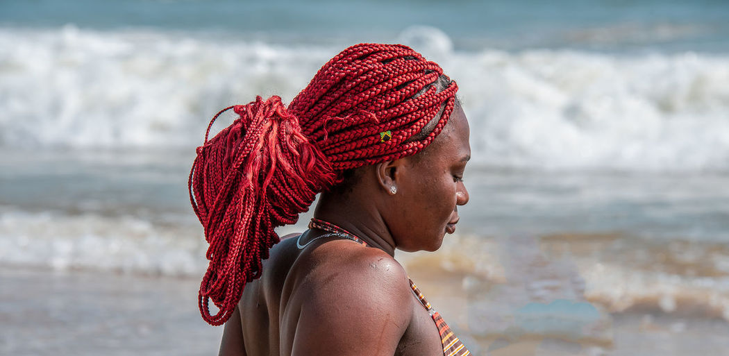 African woman with tied red rasta braided hair on a beach in ghana west africa