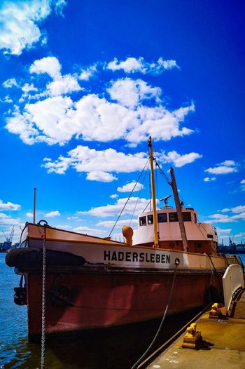 Sailboat moored at harbor against sky