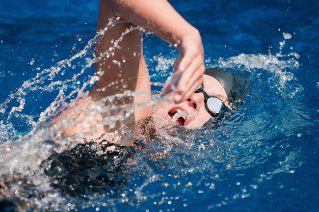 Swimmer in action 20s Attractive Female Goggles Sunlight Swimming Swimming Cap Woman Young Black Blue Caucasian Female Front Crawl Hand Lifestyles One Person Outdoors Pool Splash Sport Swimming Pool Swimwear Water Wet