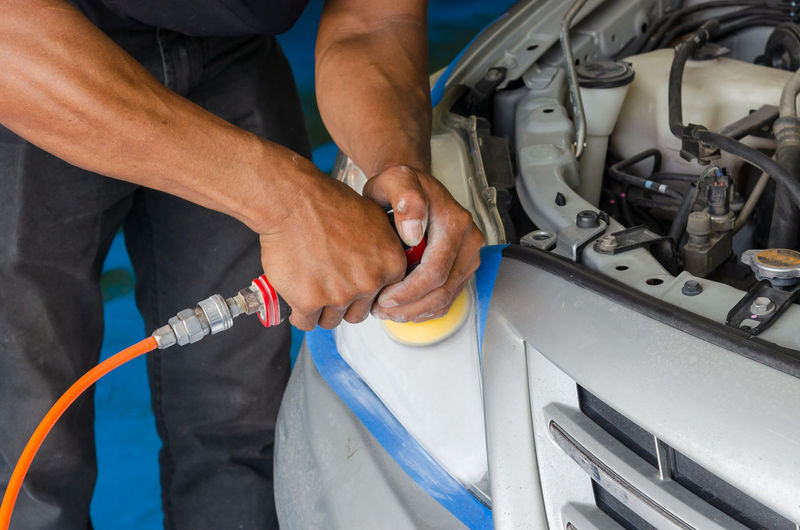 Midsection of man polishing car in garage