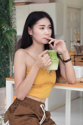 Portrait of young woman holding drink sitting on table