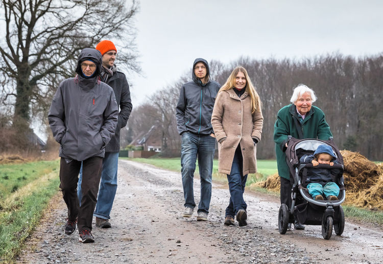 Full Length Of Family Walking On Road During Winter