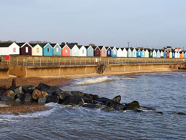 Beach huts at Southwold Beach Huts Water Multi Colored Built Structure Architecture Connection Clear Sky Rock Formation Rippled Sea Tranquil Scene Day Travel Destinations Tranquility Town Outdoors