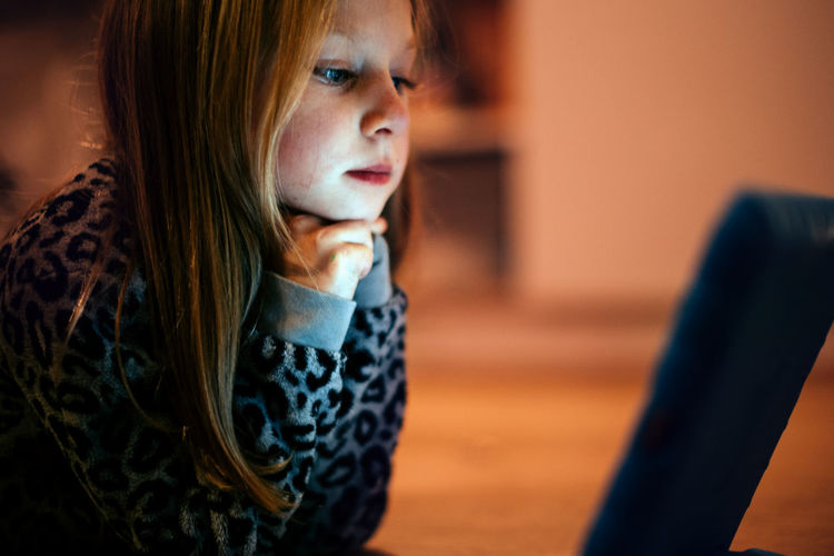 Girl watching tablet lying on the floor at home