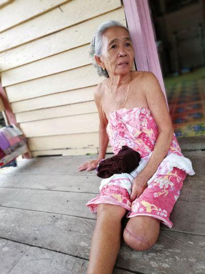 Thoughtful senior woman sitting at porch