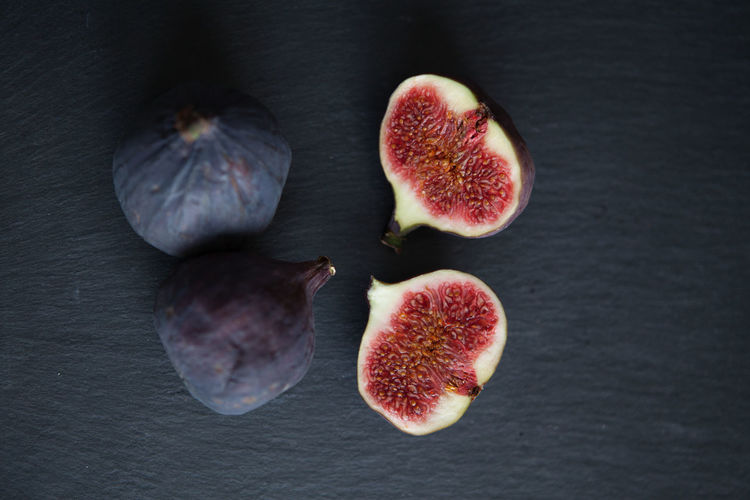 Beautiful fresh blue violet figs on dark stone background with empty copyspace close up vie from above. Fig Fruit Wellbeing Healthy Eating Freshness Still Life Food Food And Drink Indoors  No People Cross Section Group Of Objects Close-up Table Studio Shot SLICE Ripe High Angle View Halved Medium Group Of Objects Purple