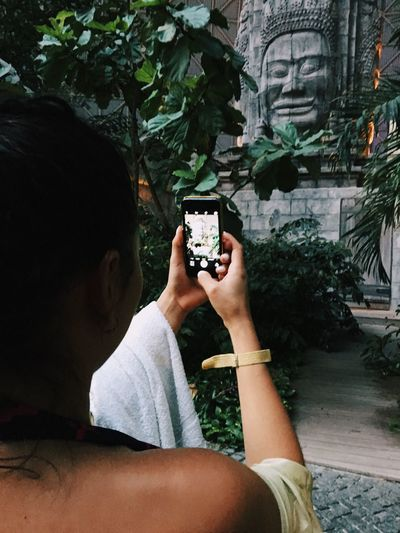 Young woman photographing through smart phone