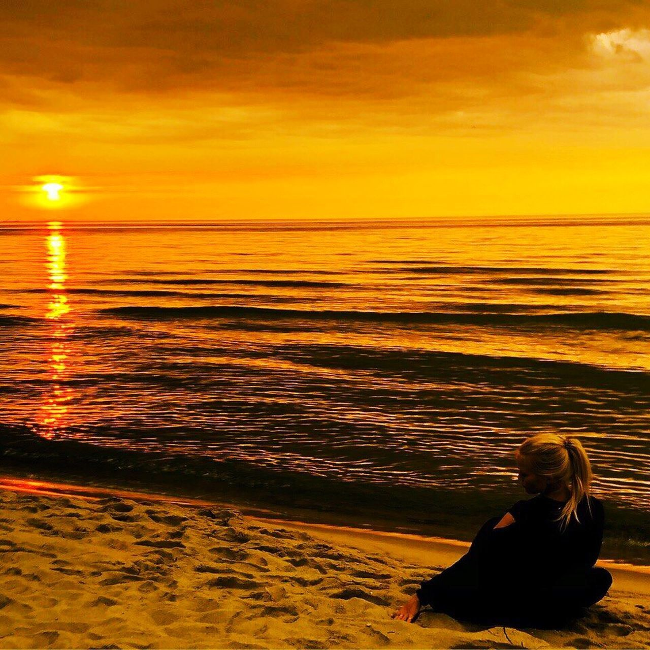 sunset, sea, sky, water, orange color, lifestyles, beauty in nature, sitting, scenics - nature, beach, land, leisure activity, one person, real people, horizon over water, nature, women, idyllic, outdoors, hairstyle