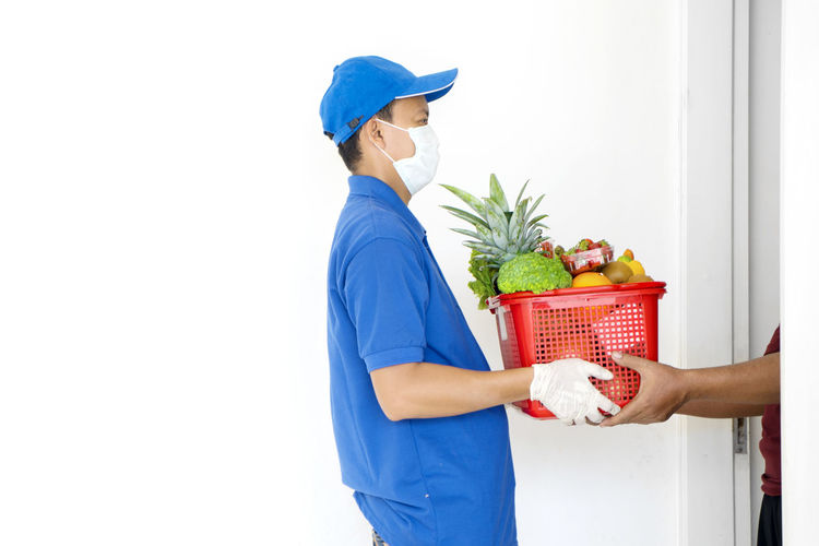 Cropped image of man receiving parcel from delivery person at home