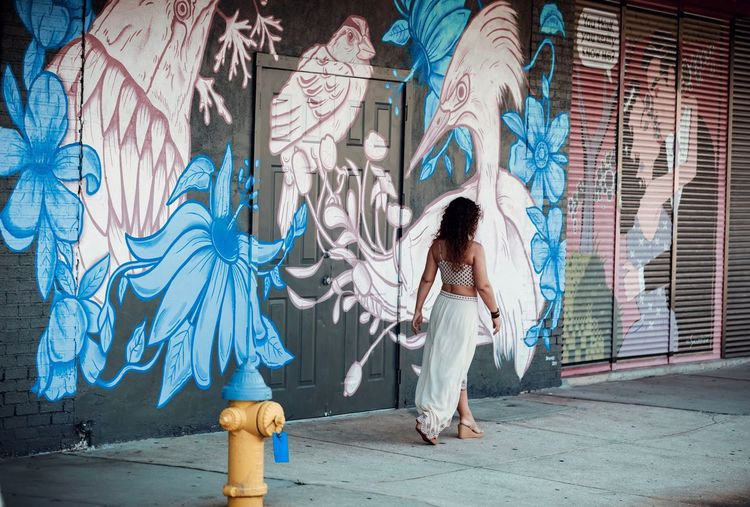 Full length of woman standing against graffiti wall