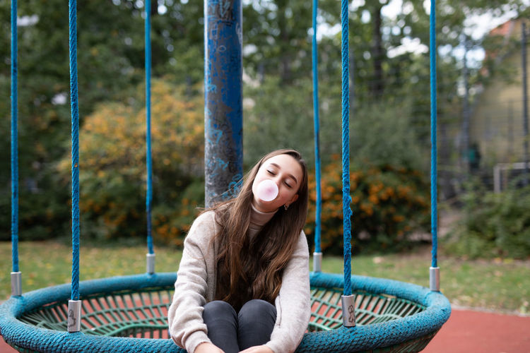 Smiling young woman blowing bubblegum while sitting in swing at playground