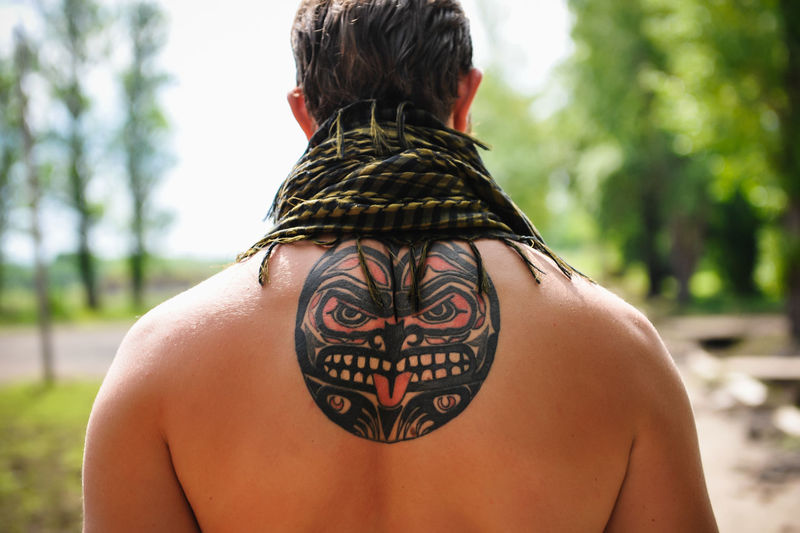 Rear view of shirtless man with tattoo on back