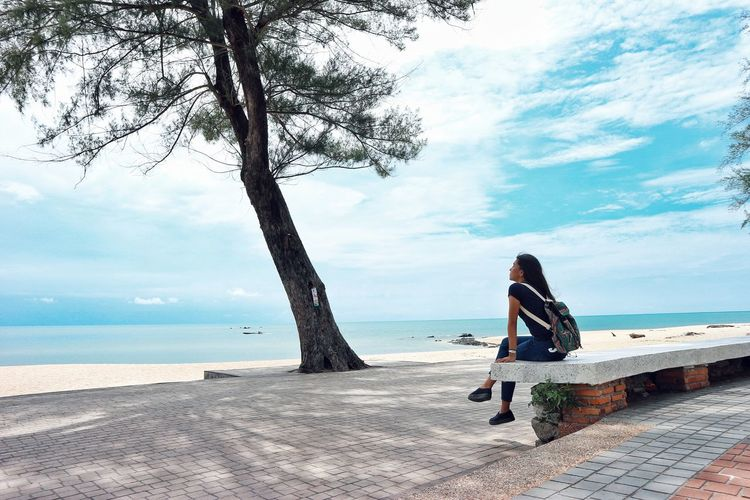 Woman Sitting On Shore Against Sky