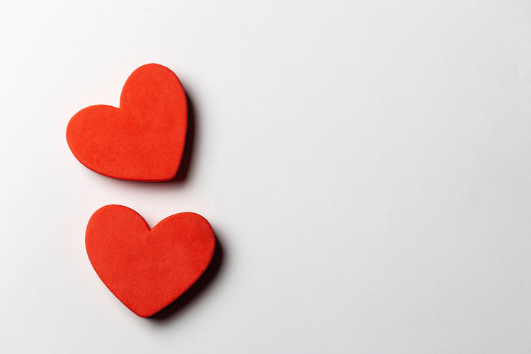 Close-up of red heart shape over white background